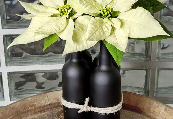 Un centro de Navidad con  botellas y ponsettias